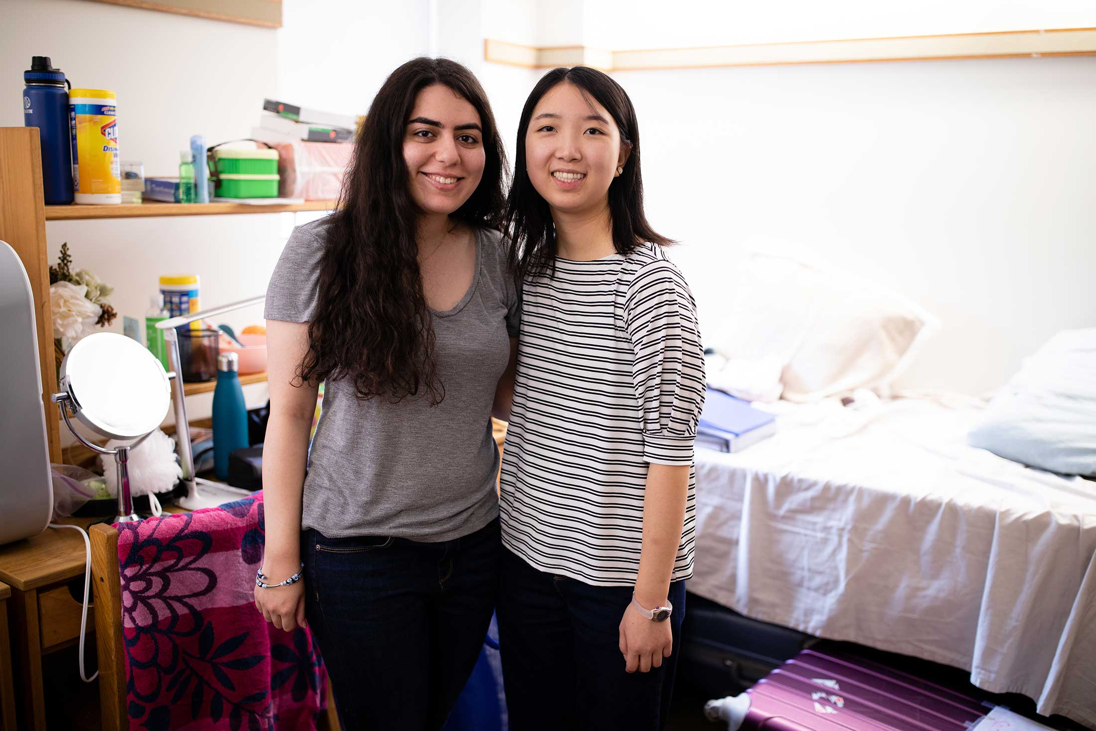 Two new roommates pose for a photo in their shared room