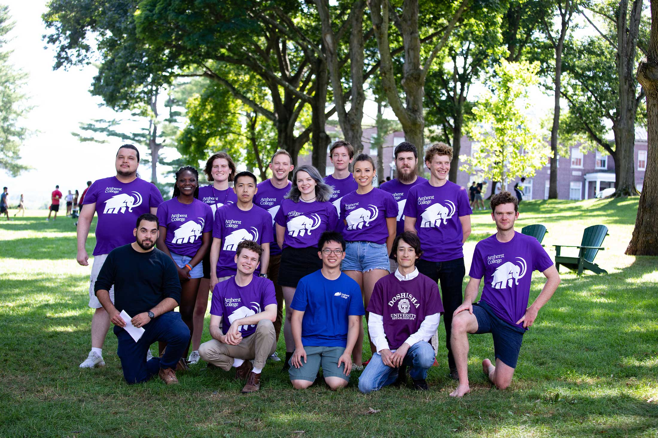 A group of transfer students -- most of them wearing purple mammoth tshirts -- pose together on the academic quad.