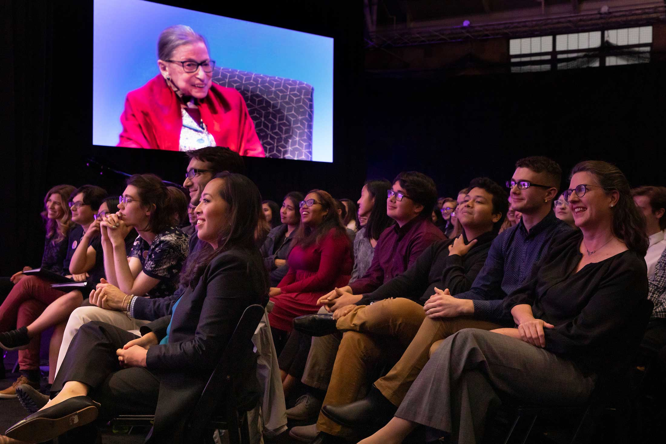 The audience listening to Justice Ginsburg who is shown on the large display screen in the venue