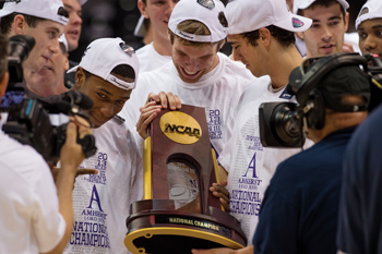 Amherst basketball players holding NCAA trophy