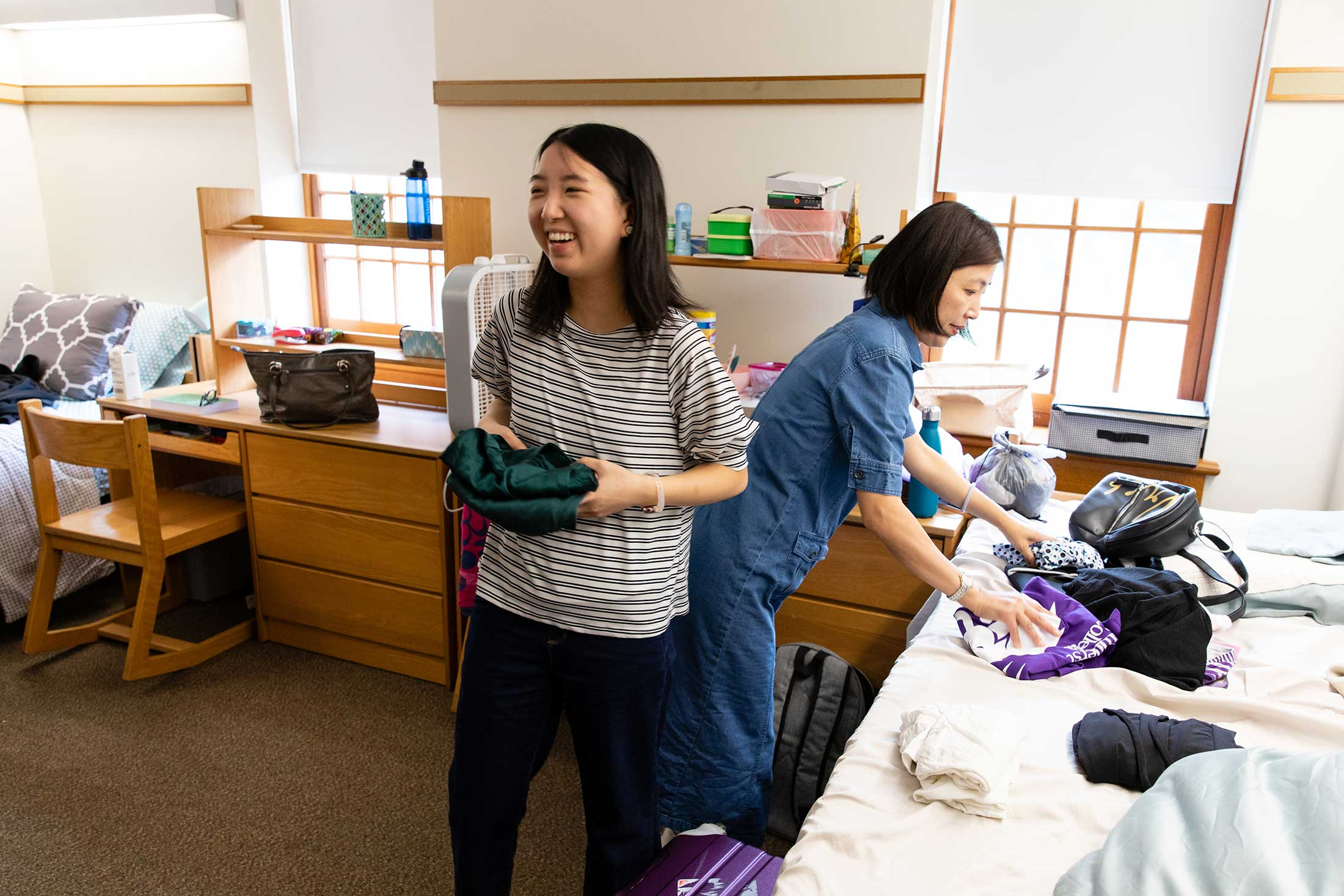 A new student unpacks her belongings in the residence hall with the help of her mother