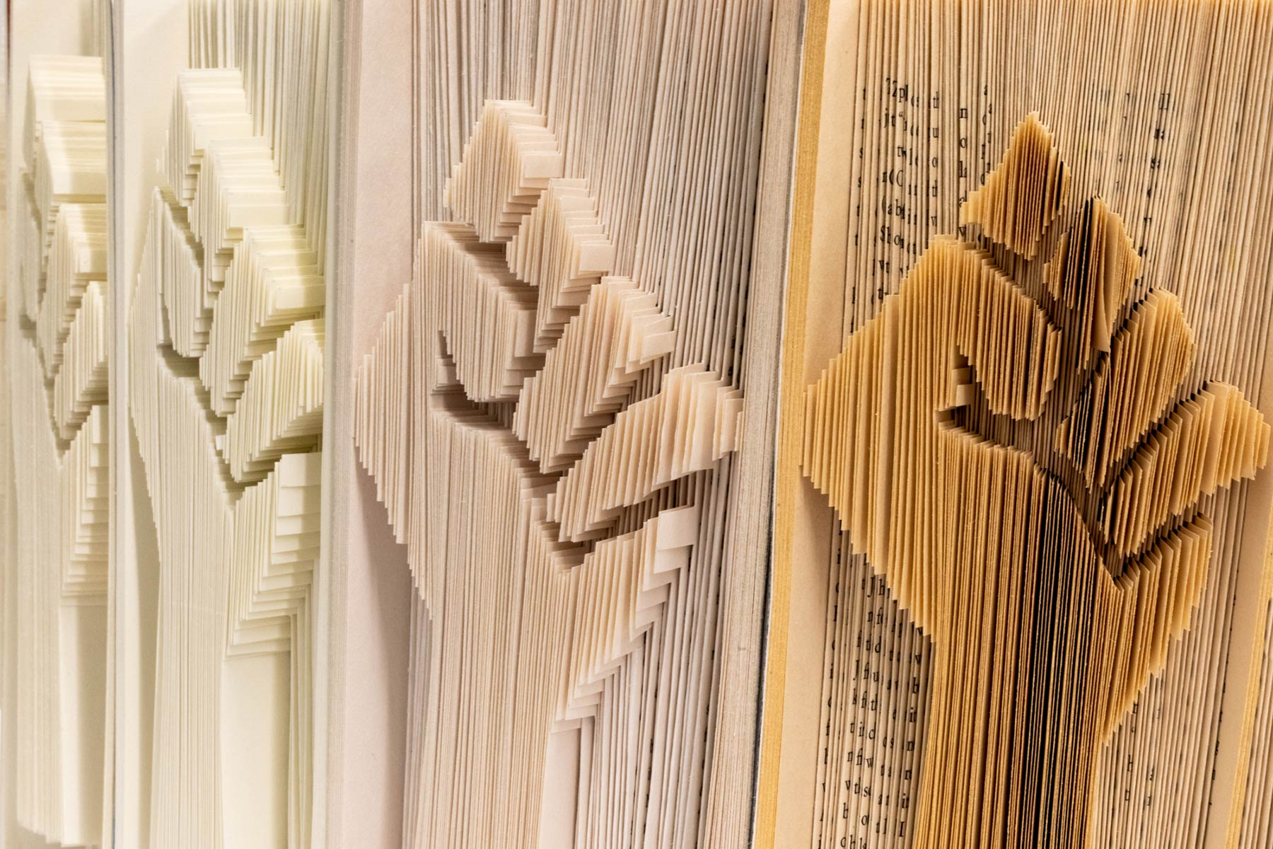 a close up of fine book sculpture showing a closed fist carved into the pages of the book