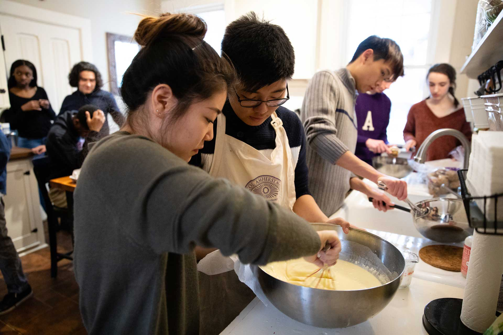 Students mixing and stirring ingredients in a bowl
