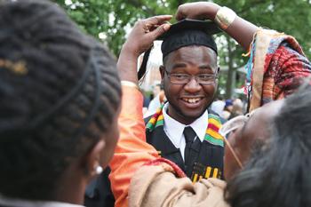 A relative adjusts an Amherst grad's cap.