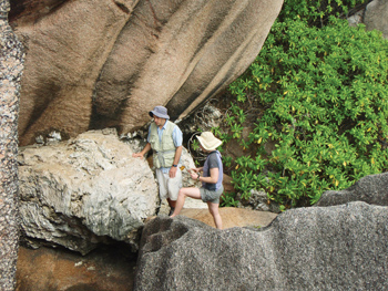 Dutton and colleague standing amid large rocks and greenery