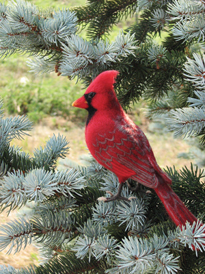 Cardinal sculpture perched in an evergreen tree