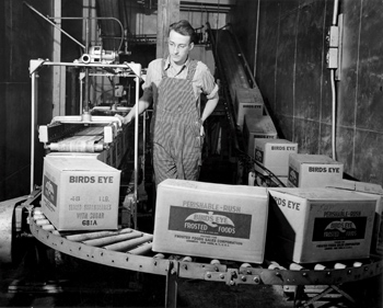 Factory worker with boxes on conveyor belt