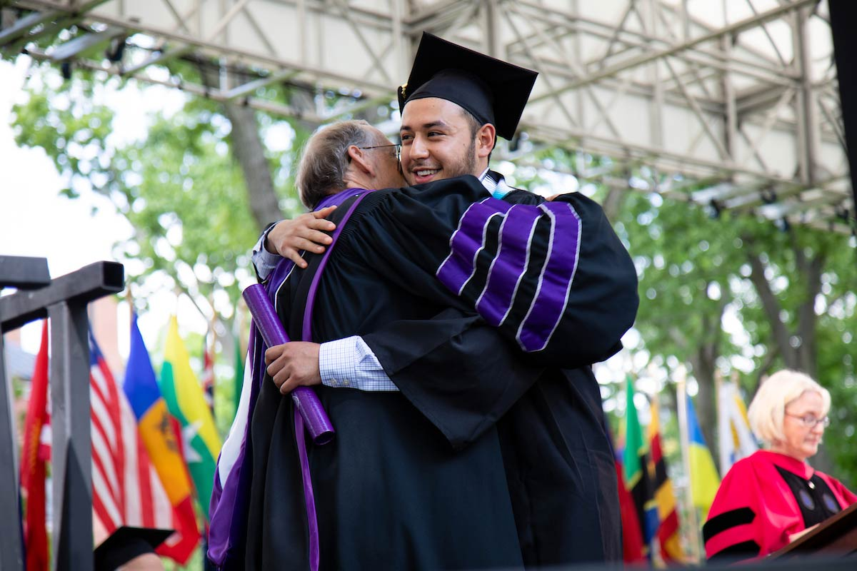 A faculty member congratulates a graduate