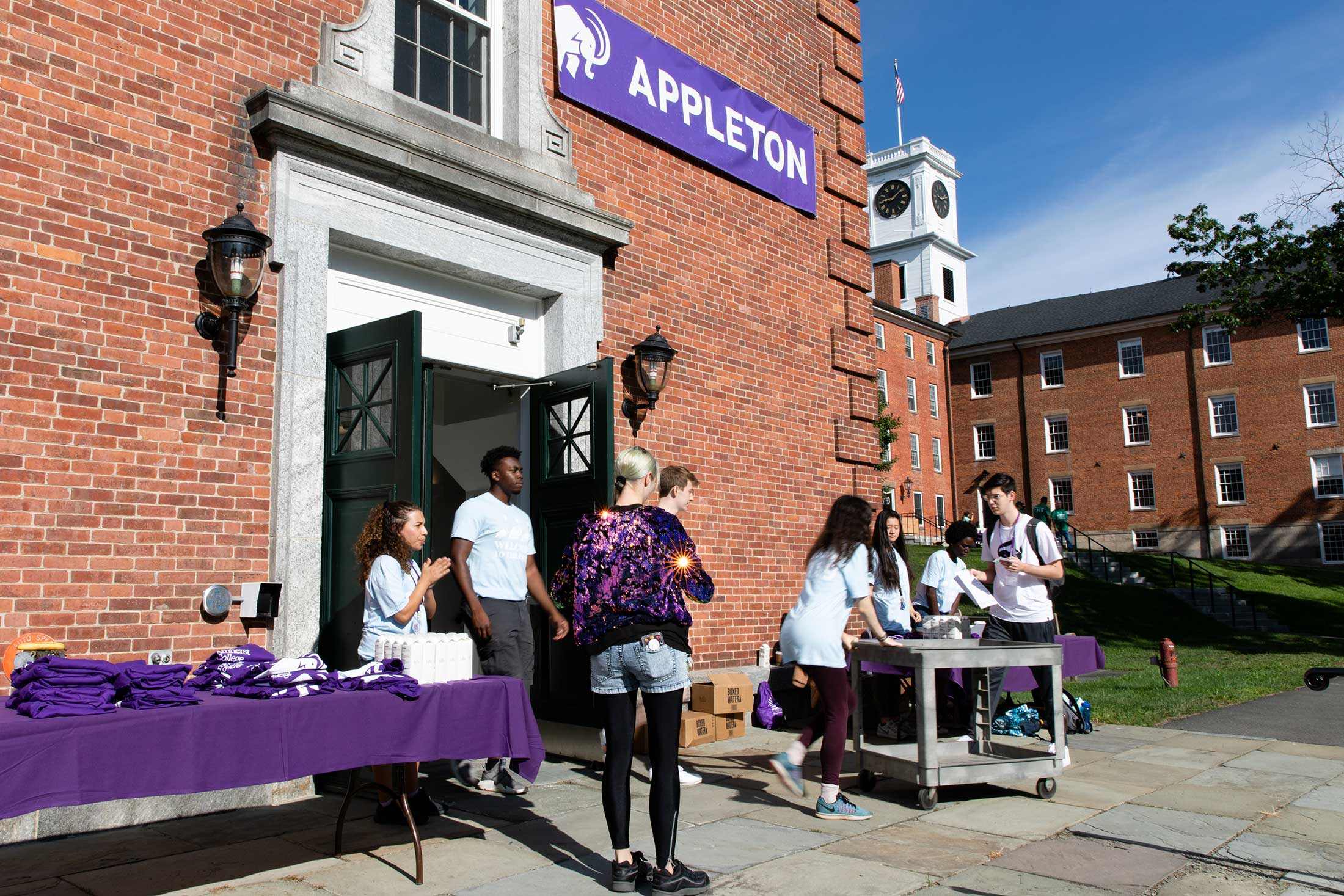 Amherst College staff greet new students arriving in front of Appleton Hall