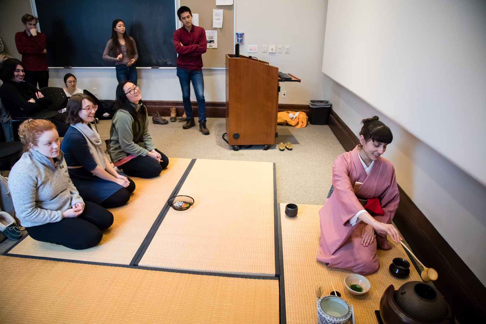 Three students kneel on a straw mat while the ceremony leader prepares tea