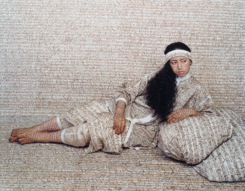 Photograph by Lalla Essaydi of a woman lying with elbow propped on pillow, surrounded by calligraphy text