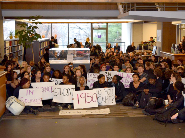 students sitting on the floor of the Frost Library lobby holding protest signs saying 1950 and Do you care?