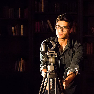 A man stands behind a video camera