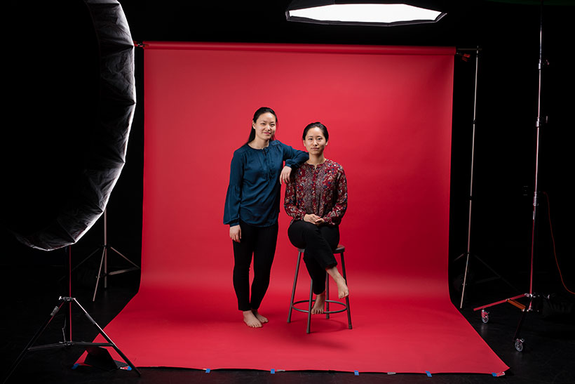 Sisters Faith and Debbie Wen pose for their portraits. Debbie is sitting on a stool and Faith stands to her right, resting her arm on her sister's shoulder.