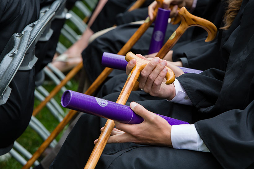 Students in commencement gowns holding canes and purple diploma tubes