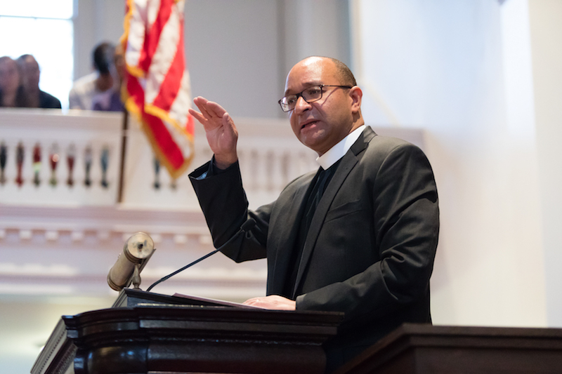 Rev. Phillip Jackson '85 at the podium in Johnson Chapel, with the American flag in the background