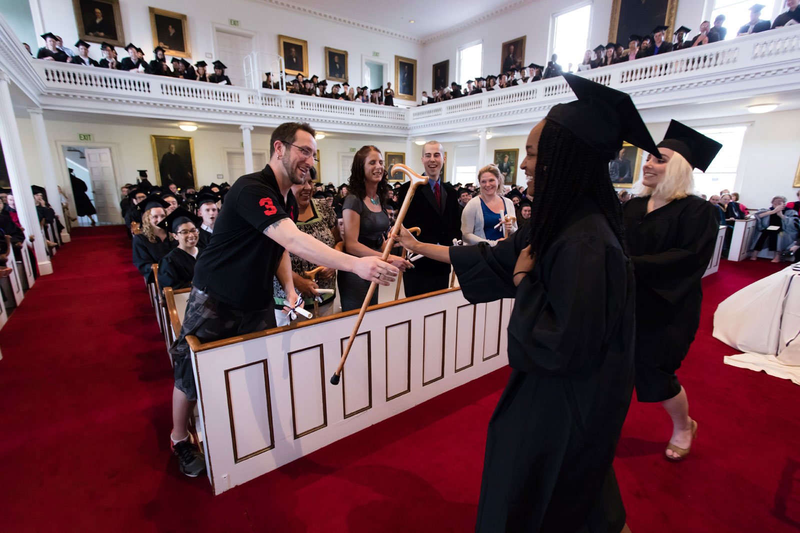 A student in regalia hands an Amherst cane to an honorary class member