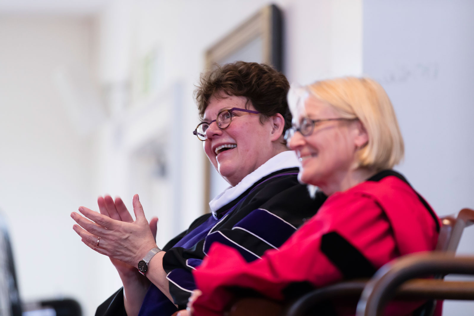 Seated on stage, President Biddy Martin and Dean of the Faculty Catherine Epstein applaud
