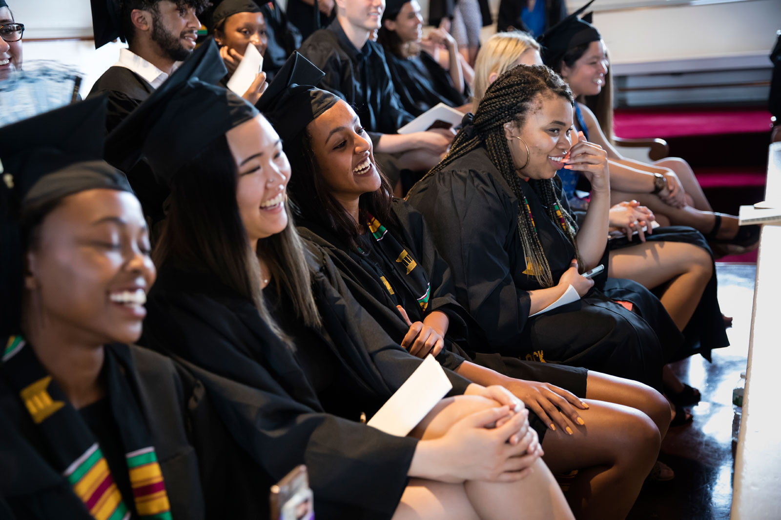 A row of students sitting in Johnson Chapel smiling