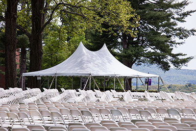 A white tent and rows upon rows of white chairs set up outside