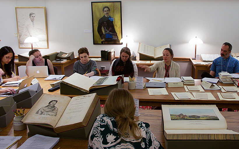 A group of people sitting around a conference table with large books open on the table