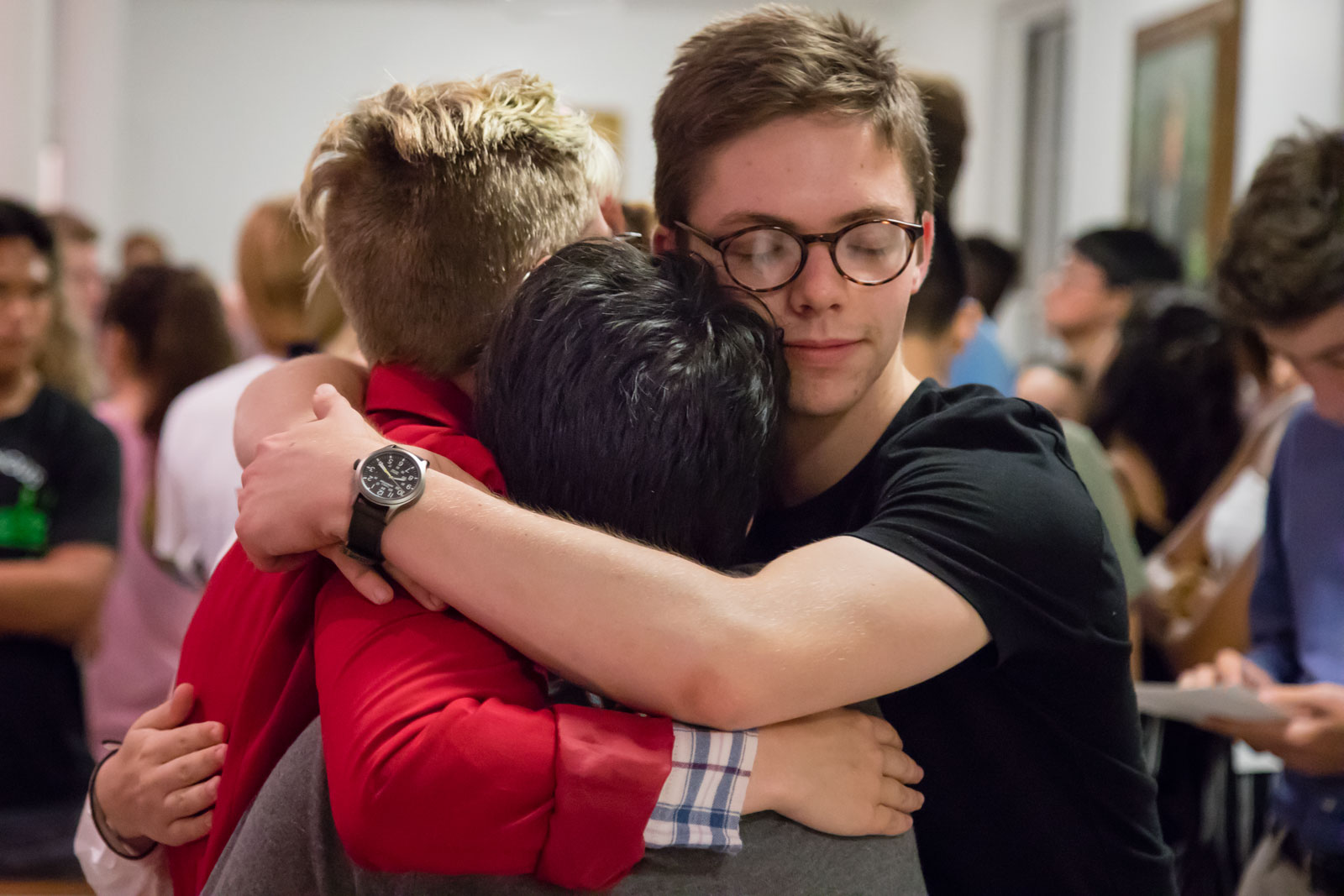 Three students hug