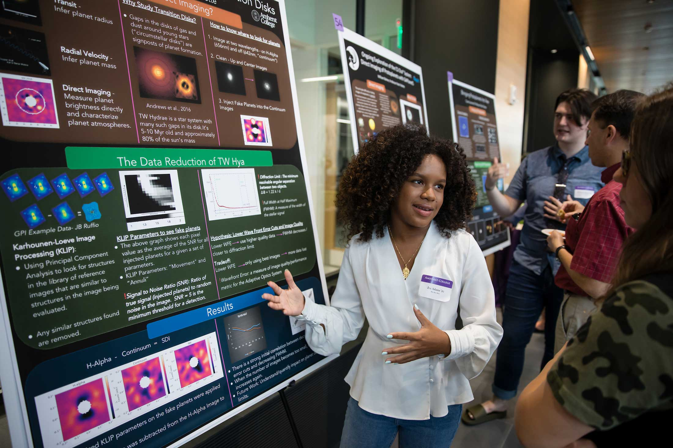 A student describes her summer research which is illustrated on a large poster