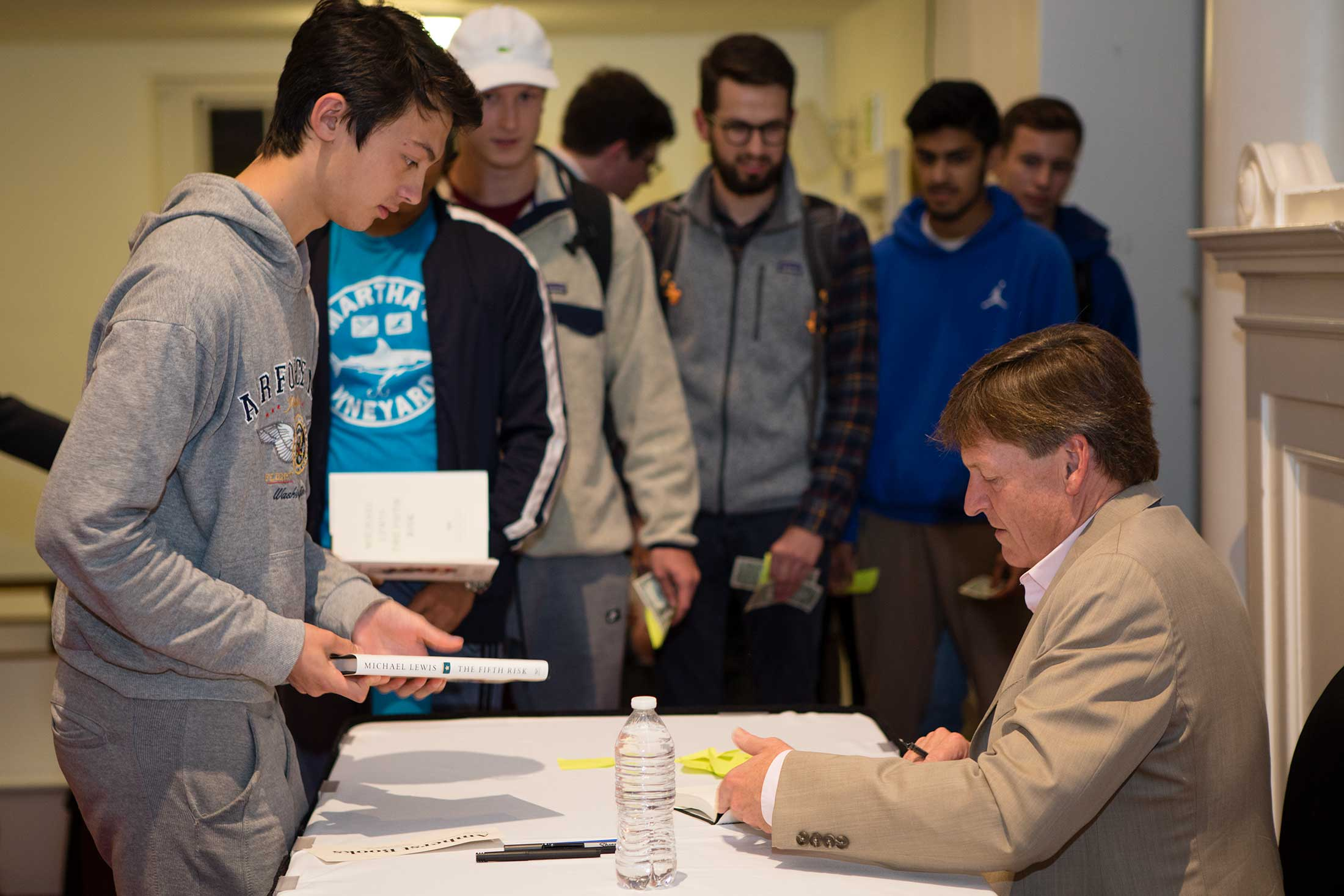 Student wait in line to get copies of Michael Lewis' book signed by the author.