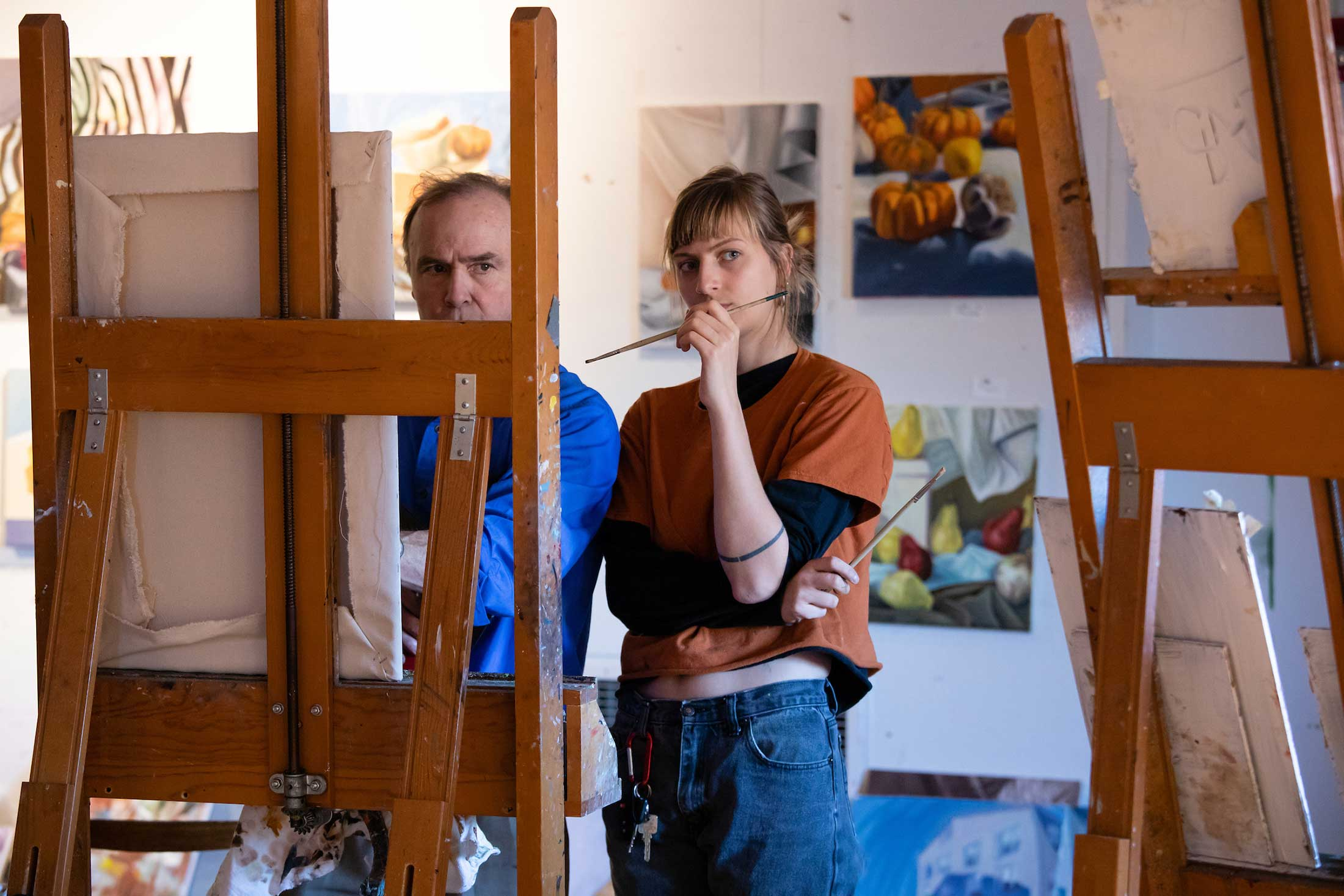 Two people stand before an easel contemplating a painting in progress