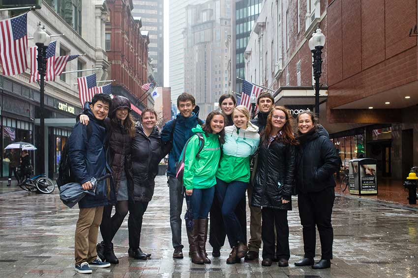 Amherst students standing outside in the rain in Boston