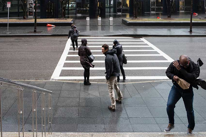 Amherst students crossing a street in Boston on an extremely rainy and windy day