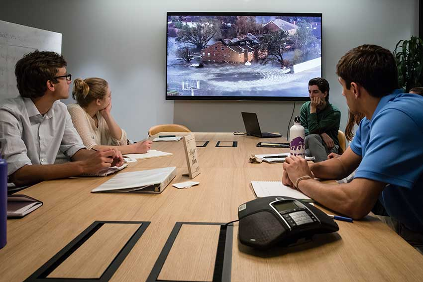 Amherst students and instructors sitting around a conference table
