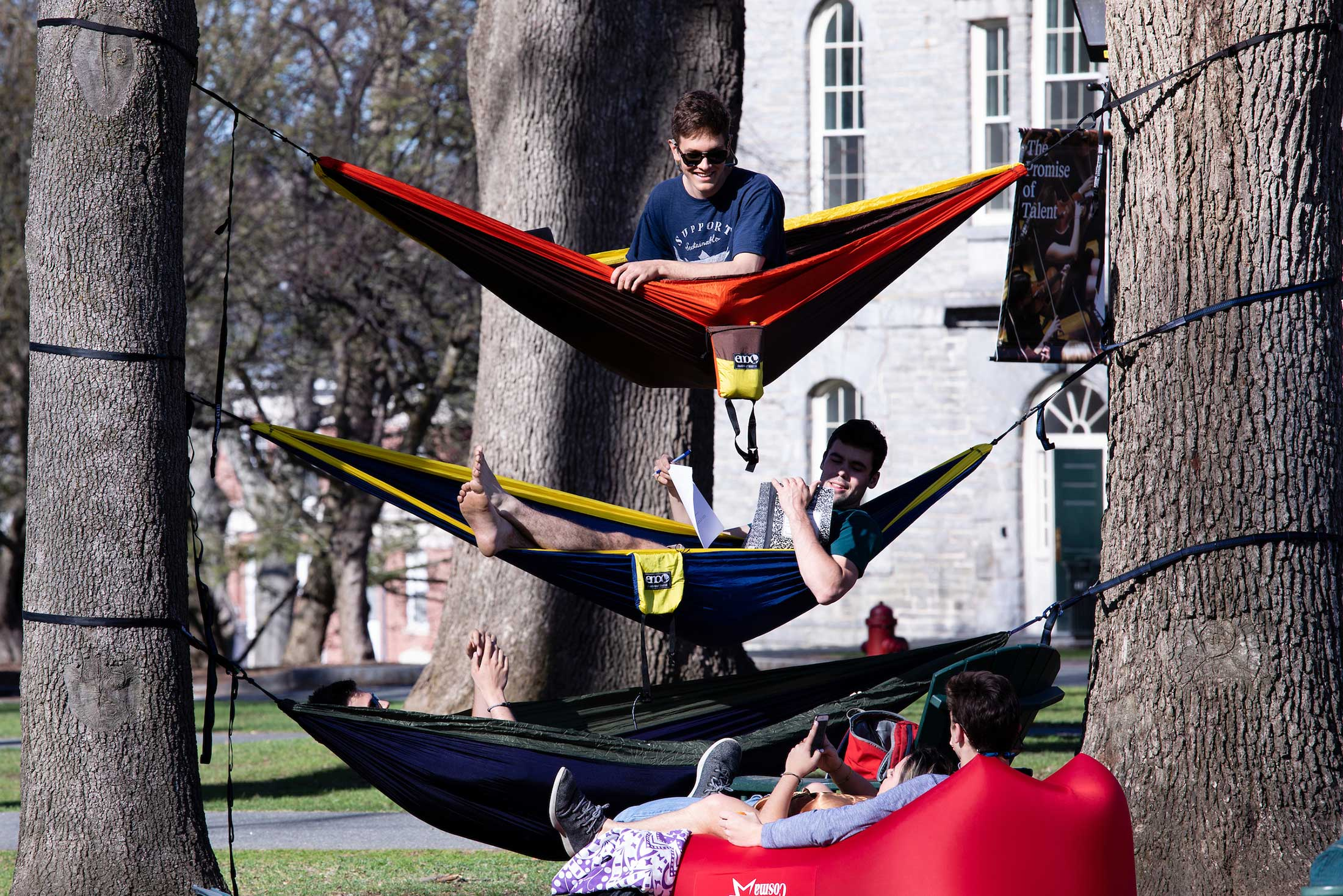 Three students relax in hammocks on the Amherst College campus