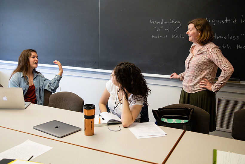 Sara Brenneis speaking to two female students in a seminar class