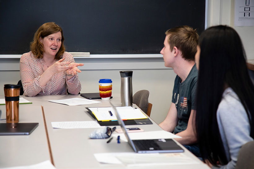 Professor Sara Brenneis seated at a seminar table with two students