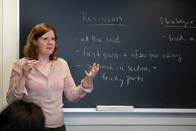 Professor Sara Brenneis stands before a blackboard covered with writing, speaking to her students