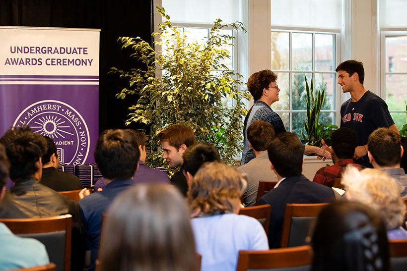 President Biddy Martin shakes the hand of an Amherst College student receiving an award