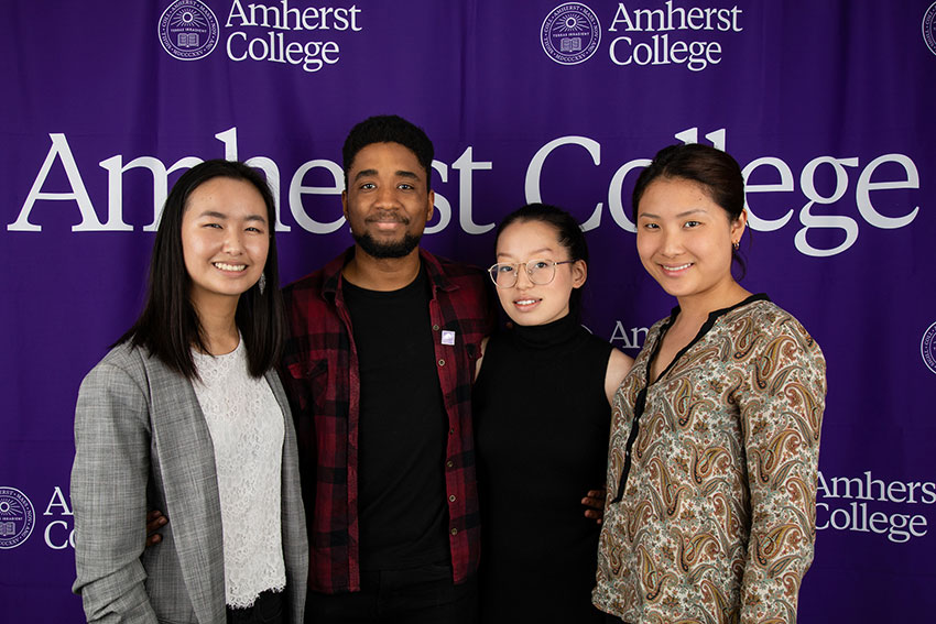Four students posing in front of an Amherst College banner