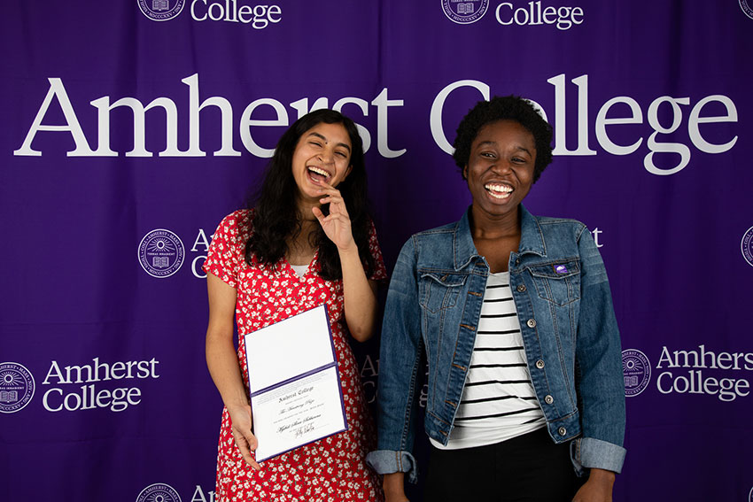 Two smiling students posing in front of an Amherst College banner