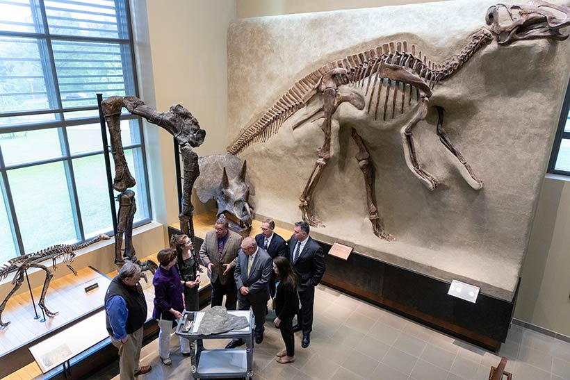 A group of people standing inside the Beneski Museum in front of a dinosaur