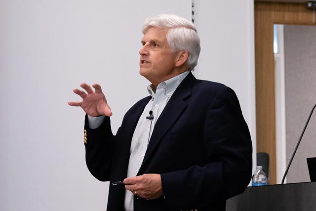David Corey speaking at a podium