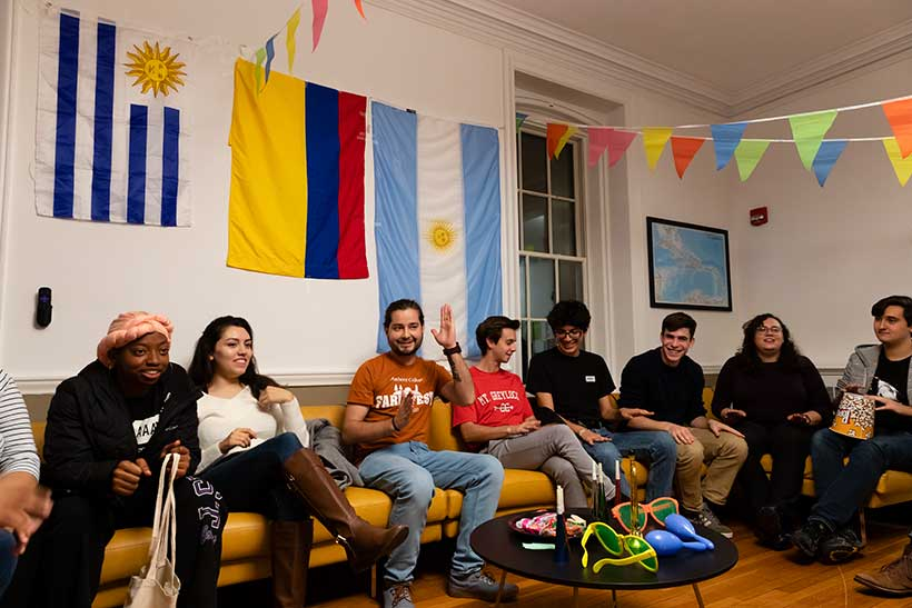 College students gathered in a lounge decorated with flags from various countries