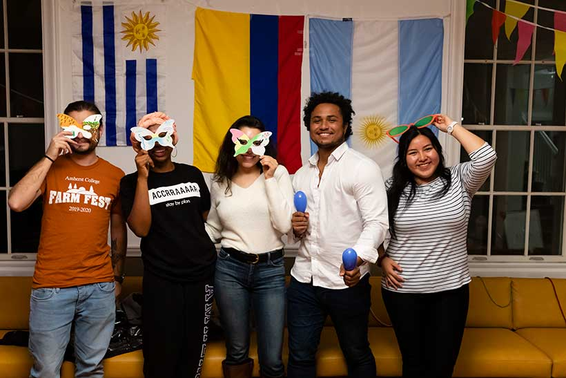 Five people pose for a photo infront of international flags, three of them are holding masks to their faces