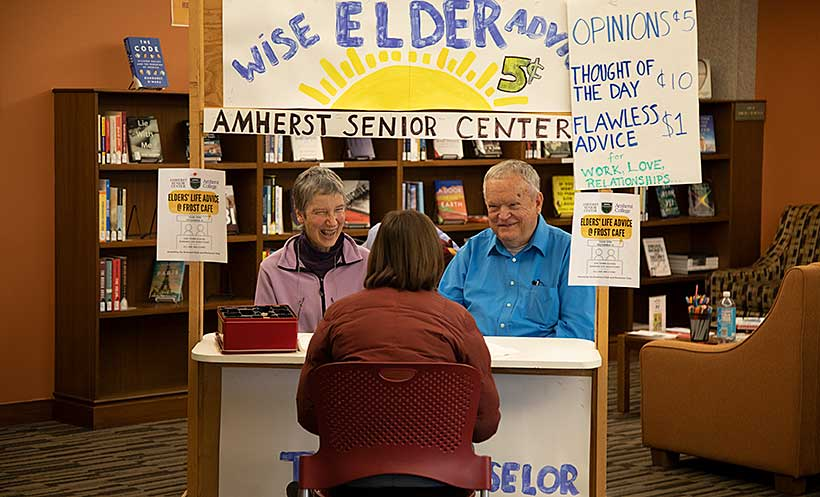 Two people sit before an information booth titles Wise Elders Advice, Amherst Senior Center