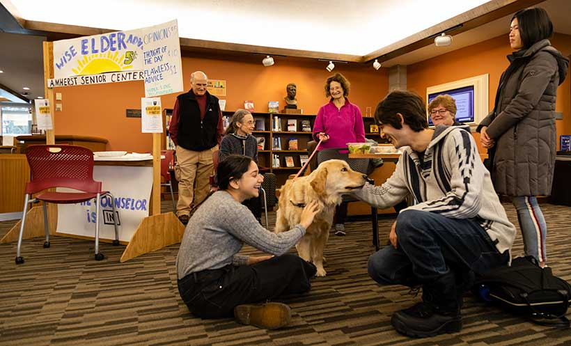Two students sit on the floor petting a golden retriever. In the background is the Wise Elders Advice booth is visible
