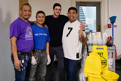 Four members of the custodial staff post together