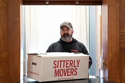 Staff member transporting a box