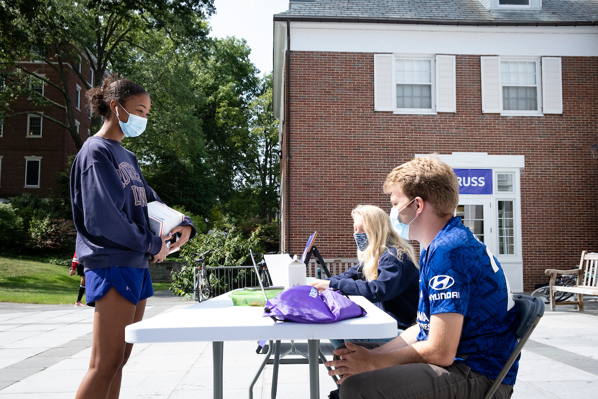 two student volunteers sit at a table to help other students register to vote