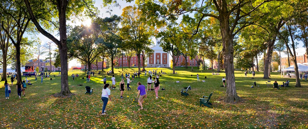 students playing games and relaxing on the quad with sun shining through autumn trees