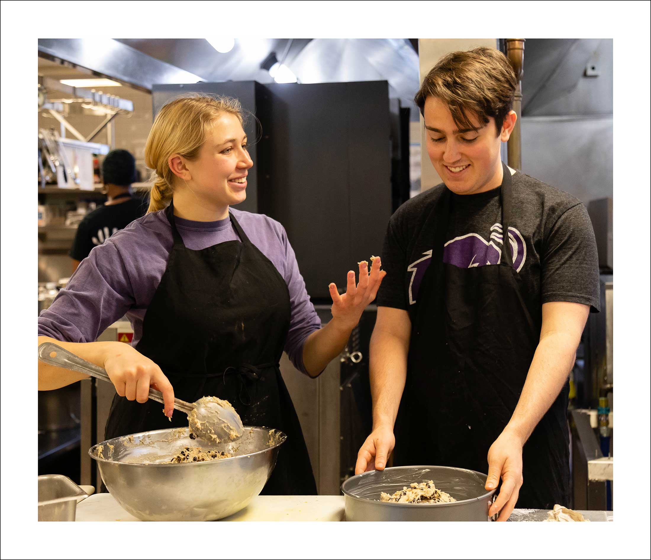 A young man and woman wearing black aprons stir ingrediants in large silver bowls
